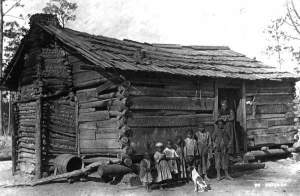1890's... Family with dog outside a log home